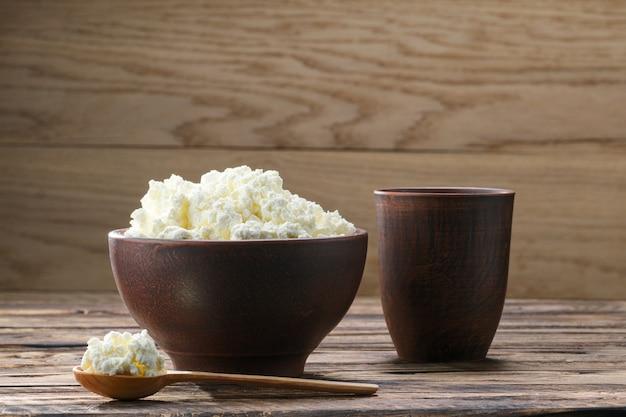 Ricotta fresca in ciotola di argilla con un cucchiaio di legno con un bicchiere di latte sul legno rustico