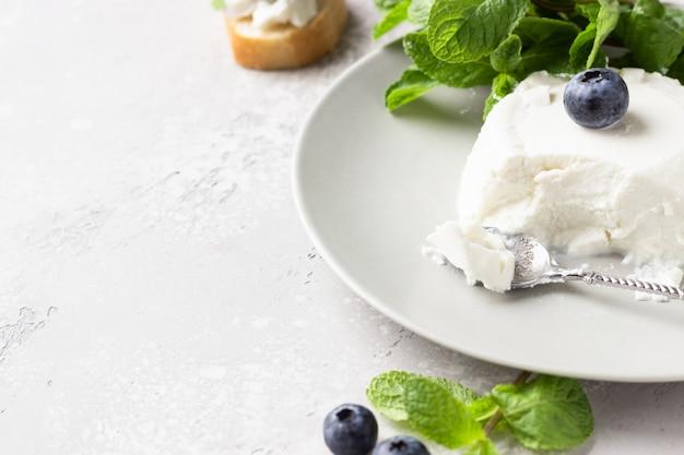 Ricotta italiana sul piatto grigio con mirtilli e menta
