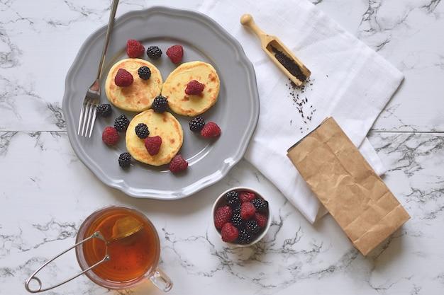 Ricotta pancakes colazione salutare senza glutine lampone mora foglia di tè tazza di marmo vista dall'alto piatto lay