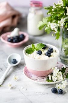 Ricotta per la colazione con mirtilli, panna, latte su un tavolo bianco e un ramo di fiori.