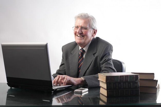 Ridendo felice uomo anziano utilizzando un computer portatile