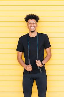 Ridendo giovane uomo nero con corda per saltare