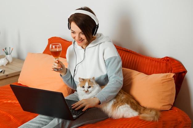 Ridere donna emotiva con le cuffie seduto sul letto con un gatto a un computer portatile in una riunione online con un bicchiere di vino.