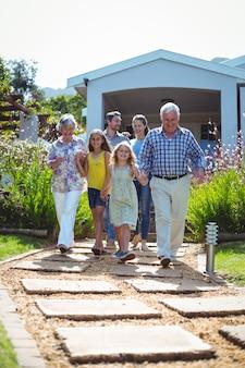 Ridere famiglia di diverse generazioni che cammina sul sentiero