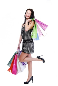 Ridere giovane donna in piedi isolato su bianco con sacchetti di colore