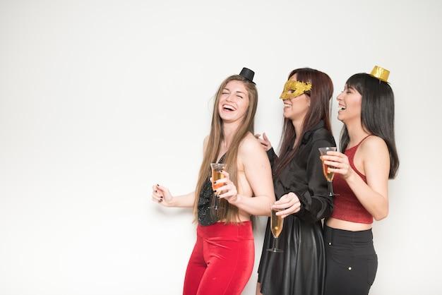 Ridere le donne in abiti da sera con bicchieri di bevande