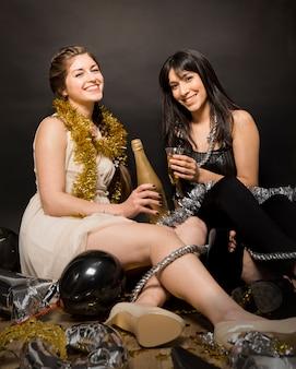 Ridere le donne in abiti da sera con un bicchiere di bibita e una bottiglia sul pavimento