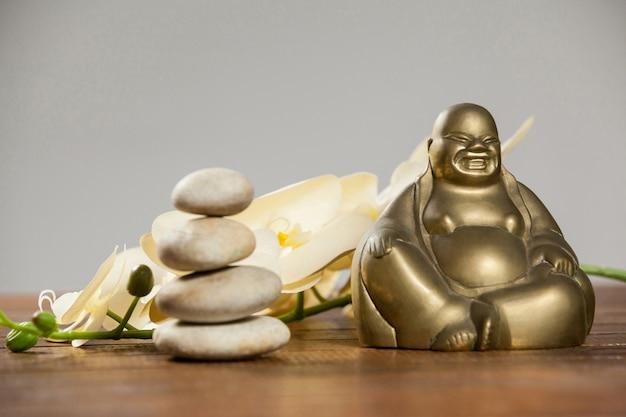 Ridere statuetta del buddha con ciottoli di pietra e fiori