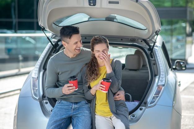 Ridere uomo e donna con caffè vicino a un'auto