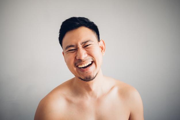 Ridi la faccia dell'uomo asiatico in ritratto topless isolato su sfondo grigio.