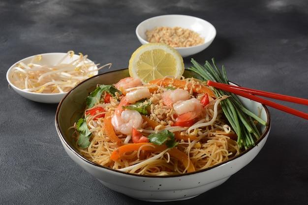 Riempi il piatto tailandese tradizionale tailandese con le tagliatelle di riso, i gamberi e le verdure fritti su una superficie scura, copia lo spazio