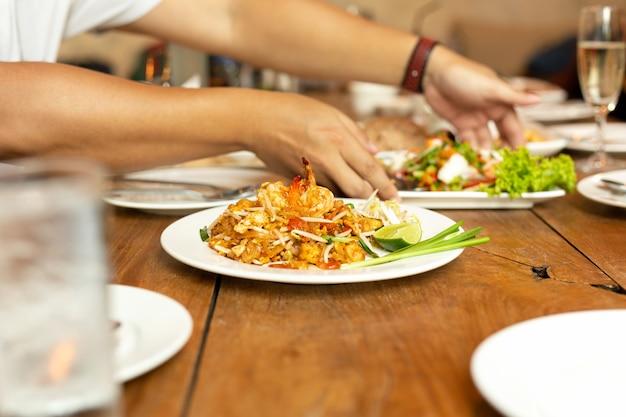 Riempia le tagliatelle tailandesi con gamberetto sul piatto del briciolo sulla tavola di legno in ristorante.