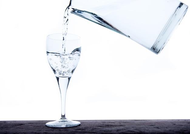Riempiendo il bicchiere d'acqua della brocca