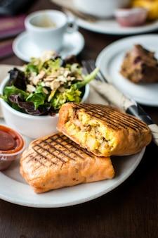 Riempire il burrito della prima colazione con insalata in un coffeeshop