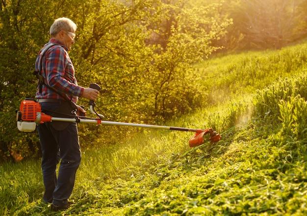 Rifinitore di falciatura - erba di taglio del lavoratore nell'iarda verde al tramonto.