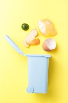 Rifiuti organici e cassonetto su uno sfondo giallo, il concetto di raccolta differenziata