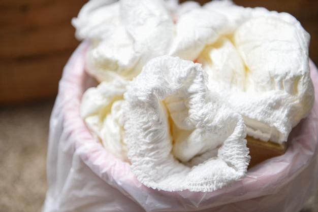 Rifiuti pannolini, pannolini sporchi in un secchio della spazzatura smaltimento di pannolini per neonati usati
