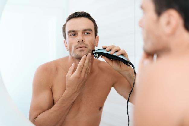 Riflessione a specchio di denti di pennello uomo in bagno.