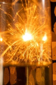 Riflessione del fuoco d'artificio del primo piano sul vetro del champagne