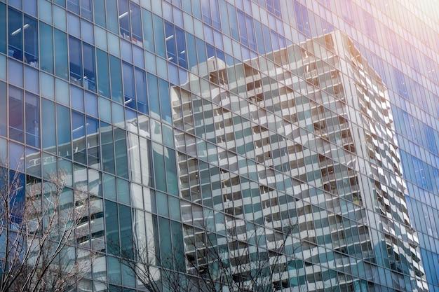 Riflessione del primo piano delle costruzioni e del cielo blu luminoso sulle finestre di vetro dell'edificio per uffici con il chiarore del sole.