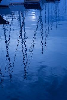 Riflessione dell'acqua blu dei pali delle barche delle barche a vela in onde