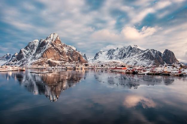 Riflessione della catena montuosa sull'oceano artico con il villaggio scandinavo sull'inverno