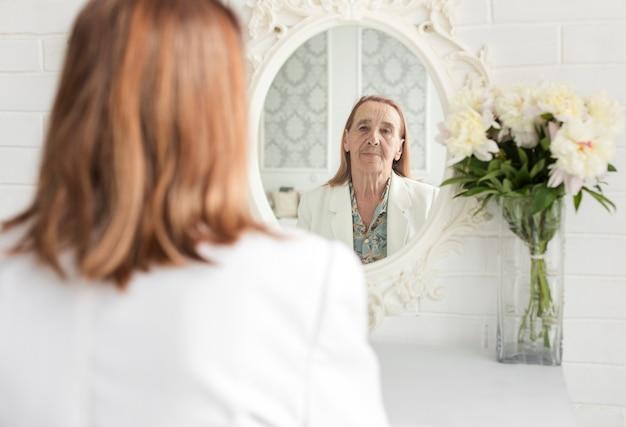 Riflessione della donna senior sullo specchio vicino al bello vaso di fiore a casa