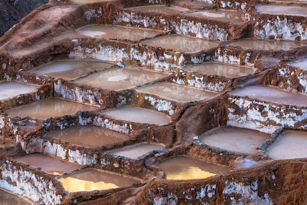 Riflessione della luce solare dell'oro nelle saline di maras, salineras de maras vicino a cusco in perù
