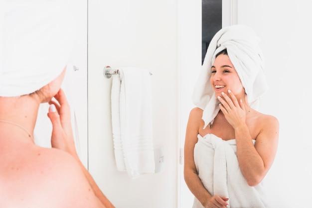 Riflessione di bella donna che osserva in accappatoio con un asciugamano sulla sua testa