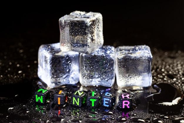 Riflessione di cubetti di ghiaccio e inverno su sfondo nero tavolo.