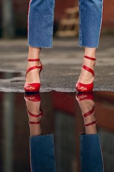 Riflessione di gambe femminili in jeans e scarpe rosse nella pozza sull'asfalto