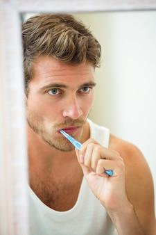 Riflessione di un giovane lavarsi i denti