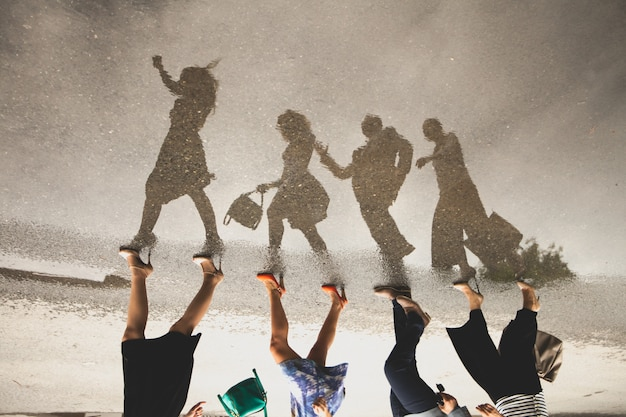 Riflessione di un gruppo di persone in una pozzanghera sulla strada.