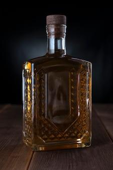 Riflessione di un teschio in una bottiglia piatta con alcool.
