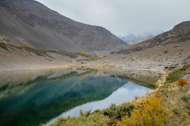 Riflessione in acqua della catena montuosa di karakoram nel lago borith, pakistan.