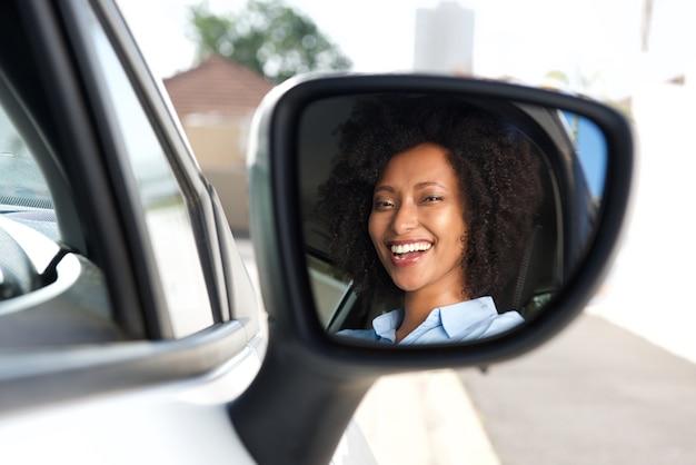 Riflessione in specchio laterale della donna africana sorridente che conduce automobile