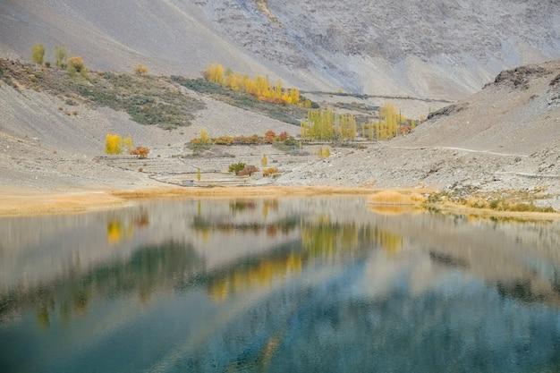 Riflessione nell'acqua della catena montuosa del karakoram nel lago borith. stagione autunnale in pakistan.