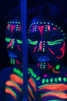 Riflessione su specchio di donna con trucco fluorescente