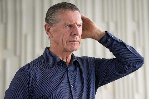 Riflessivo frown anziano grave uomo che osserva via