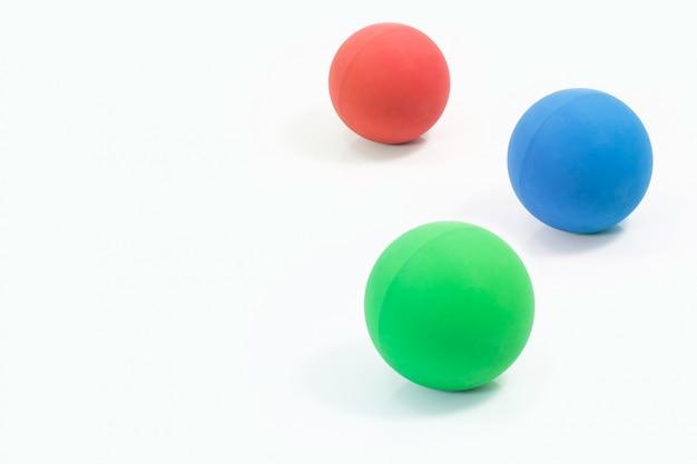 Rifornimenti dell'animale domestico circa le palle di gomma di rosso, di verde e di blu per l'animale domestico isolato