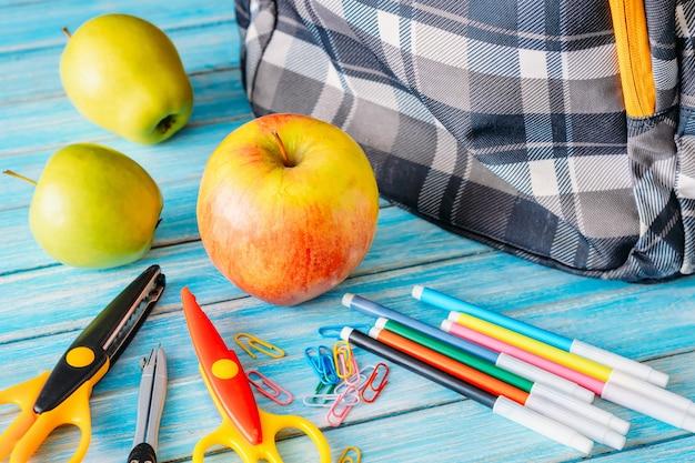 Rifornimenti dello zaino, della mela e di scuola su fondo di legno