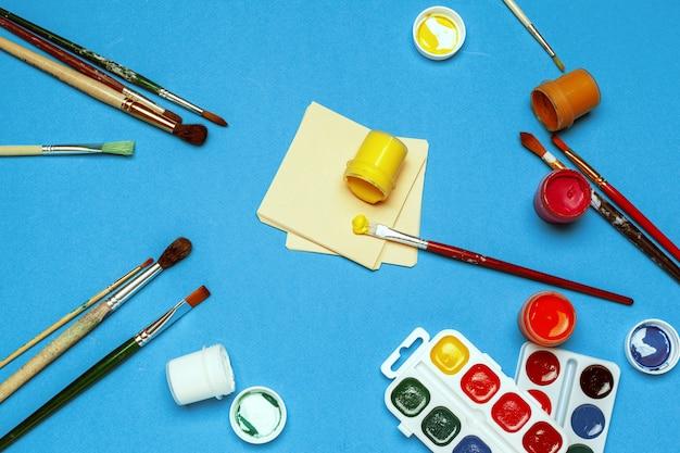 Rifornimenti di arte pitture e spazzole dell'acquerello sul blu luminoso