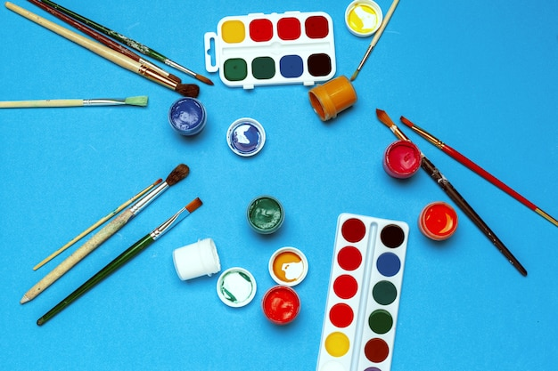 Rifornimenti di arte. pitture e spazzole dell'acquerello sul blu luminoso
