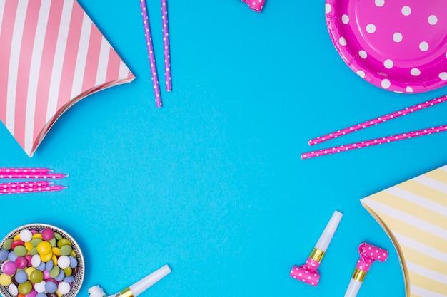 Rifornimenti di compleanno girly con lo spazio della copia su fondo blu