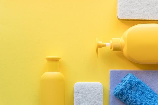 Rifornimenti di pulizia della casa piana su fondo giallo flacone spray detergente, straccio, spugna, detergente. pulizia della casa e concetto di pulizia