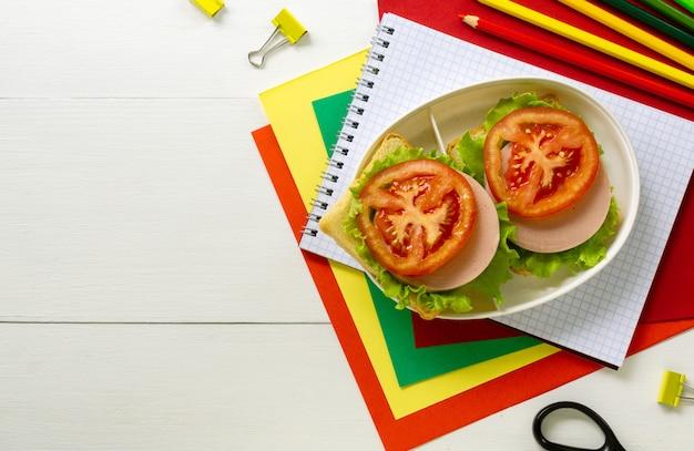 Rifornimenti di scuola e scatola di pranzo con i panini della salsiccia su un fondo di legno bianco
