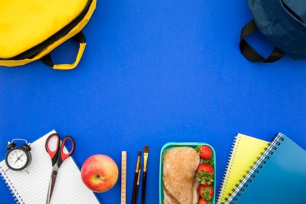 Rifornimenti di scuola e scatola di pranzo su fondo blu