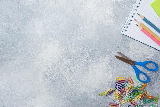 Rifornimenti di scuola, matite dei taccuini su gray con lo spazio della copia.