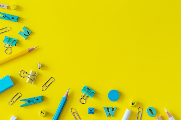 Rifornimenti di scuola multicolori su fondo giallo con lo spazio della copia