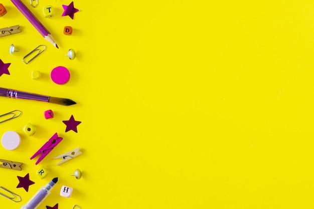 Rifornimenti di scuola multicolori su fondo giallo con lo spazio della copia.